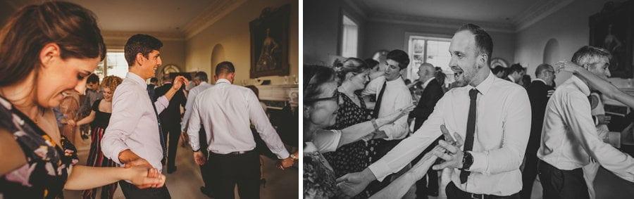 Wedding guests hold hands on the dancefloor