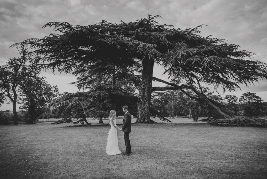 The bride and groom stand next to a tree on the lawn at Stubton Hall