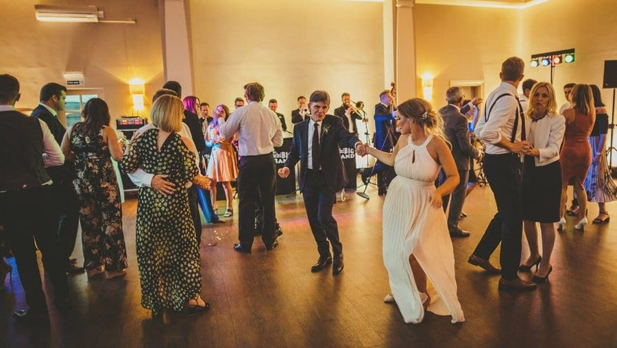 The brides sister and her father dance together on the dancefloor