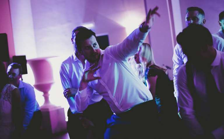 A wedding guest raises his arm and points to the ceiling on the dancefloor