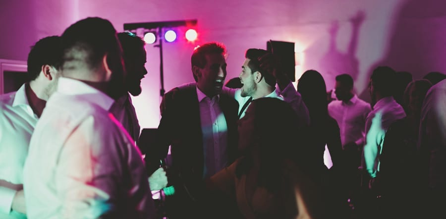 Wedding guests share a joke with each other on the dancefloor