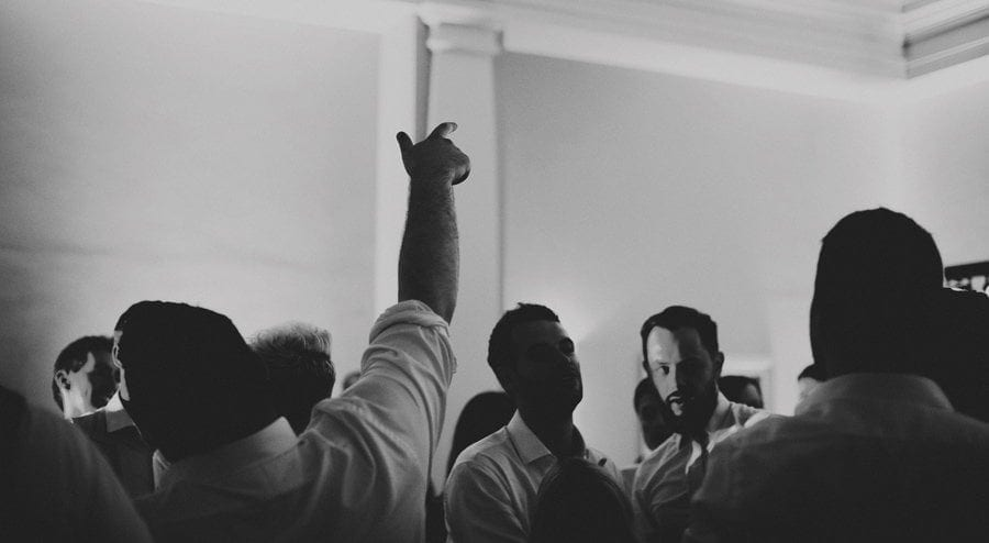 A wedding guest holds his arm up in the air