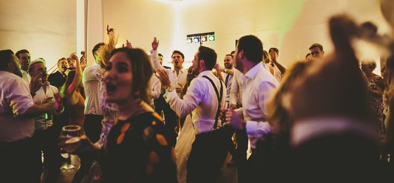 Wedding guests on the dancefloor gather together and sing songs