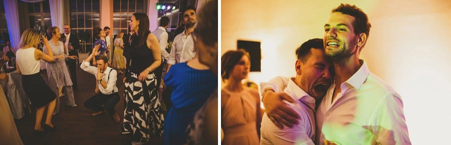The groom holds his best man on the dancefloor and shares a joke with each other