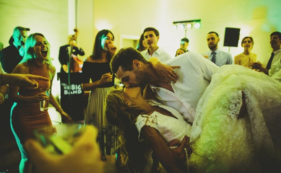 The groom picks the bride up on the dancefloor and kisses her while the wedding guests look on