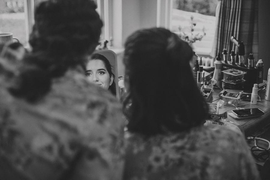 A bridesmaid smiles and looks in the mirror