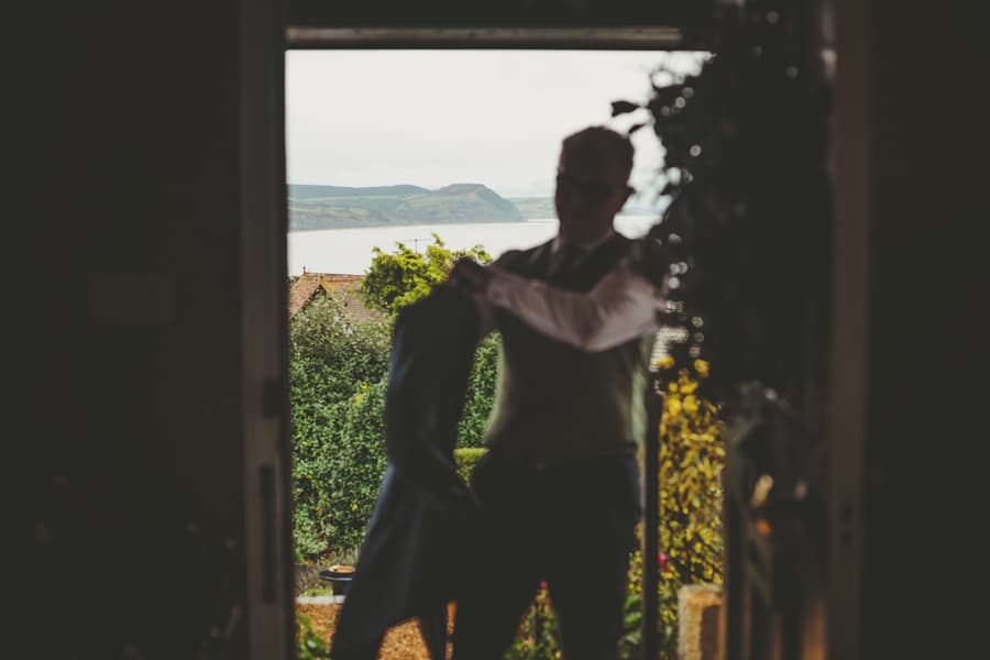 The bride's father puts on his jacket outside his house in Lyme Regis