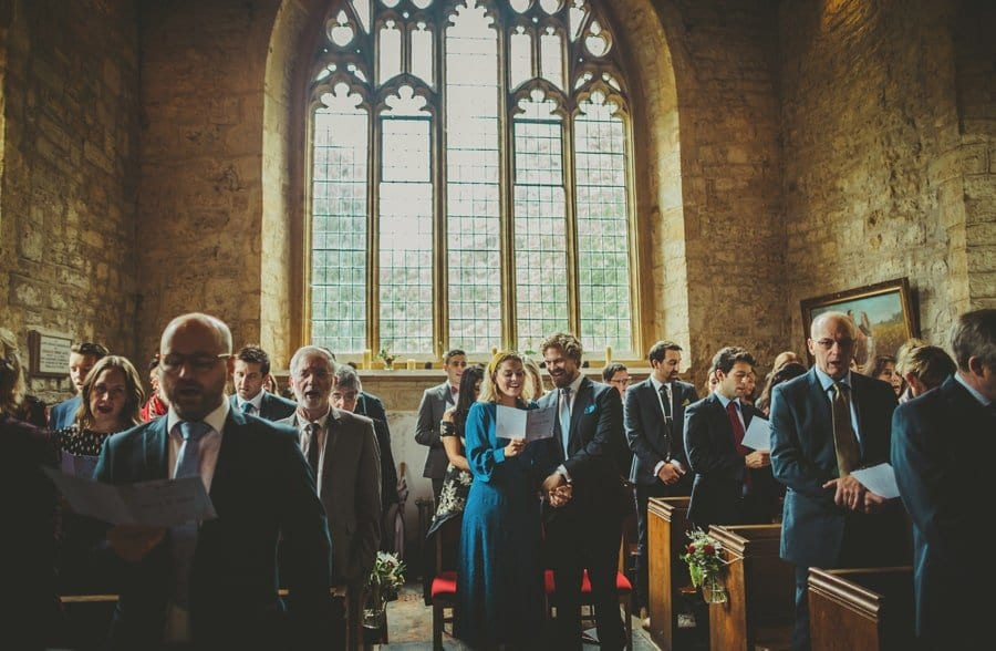 The wedding guests stand and sing a hymn in the Church