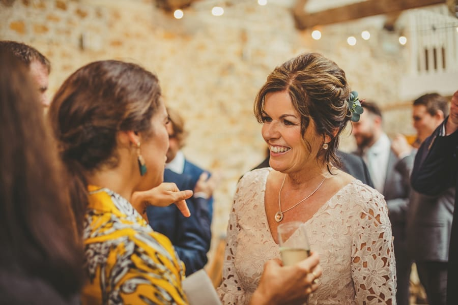 The brides mother smiles and chats with wedding guests