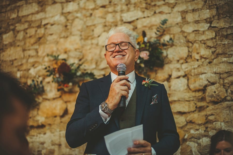 The bride's father closes his eyes and laughs during his speech