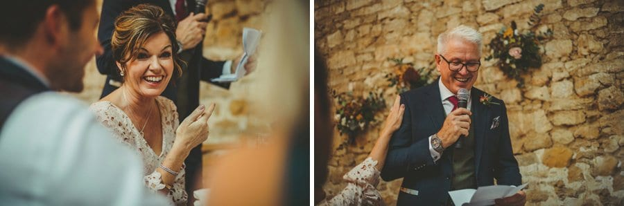 The brides mother laughs at her husband's speech in the Tithe Barn, Symondsbury