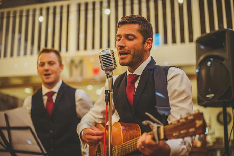 An usher plays a guitar and sings to the wedding party
