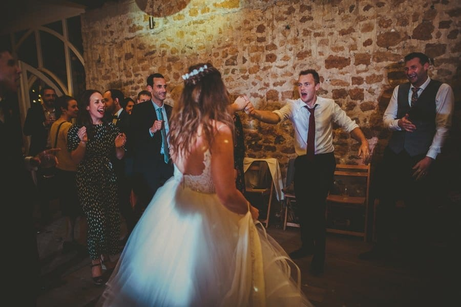 The bride dances with a wedding guest on the dancefloor