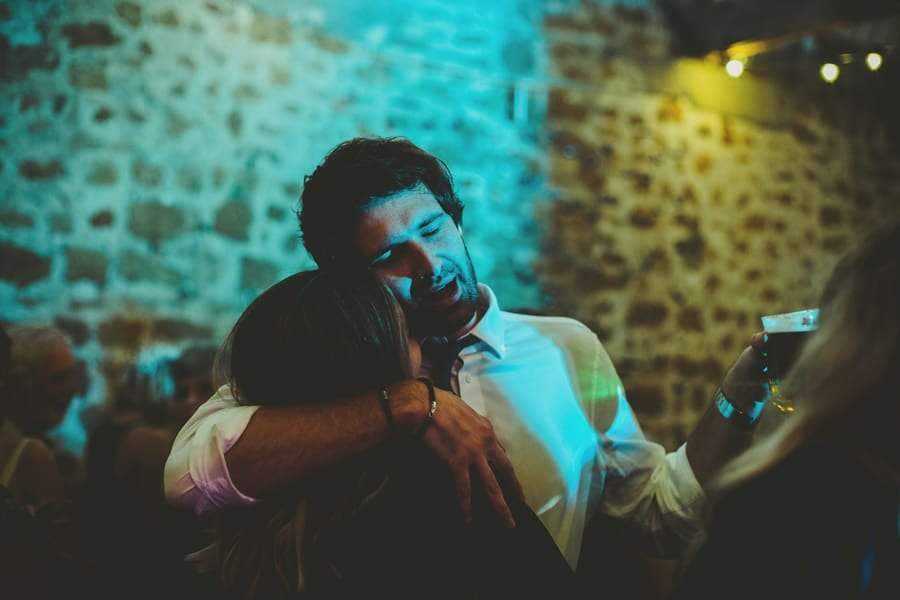 A wedding guest holds his wife on the dancefloor