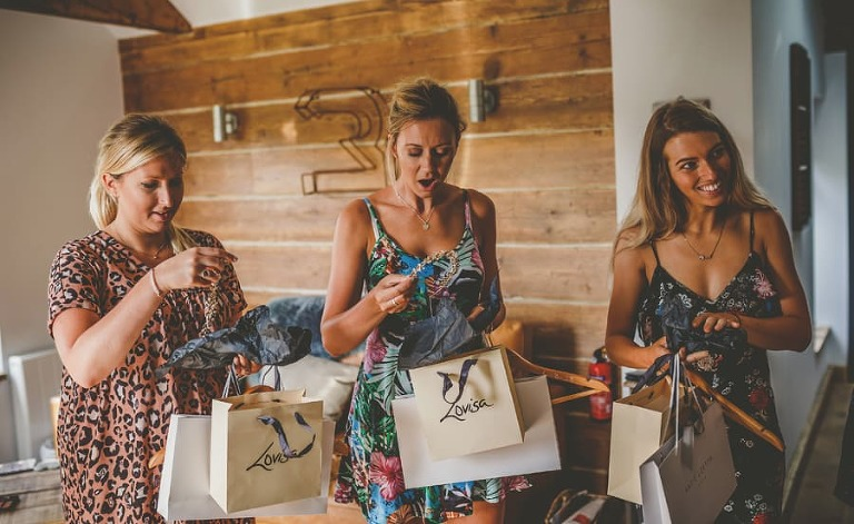 The bridesmaids open their presents given to them by the bride in the cottage at Yurt retreat