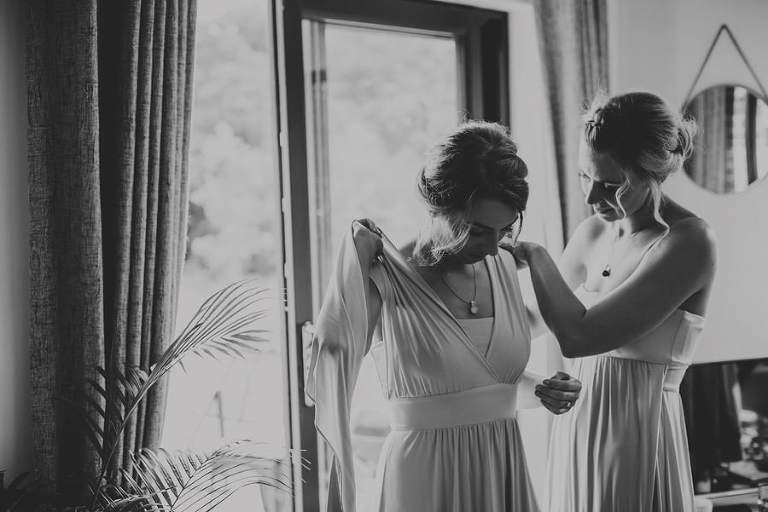 A Bridesmaid helps another bridesmaid to put on their dresses next to a window of the cottage