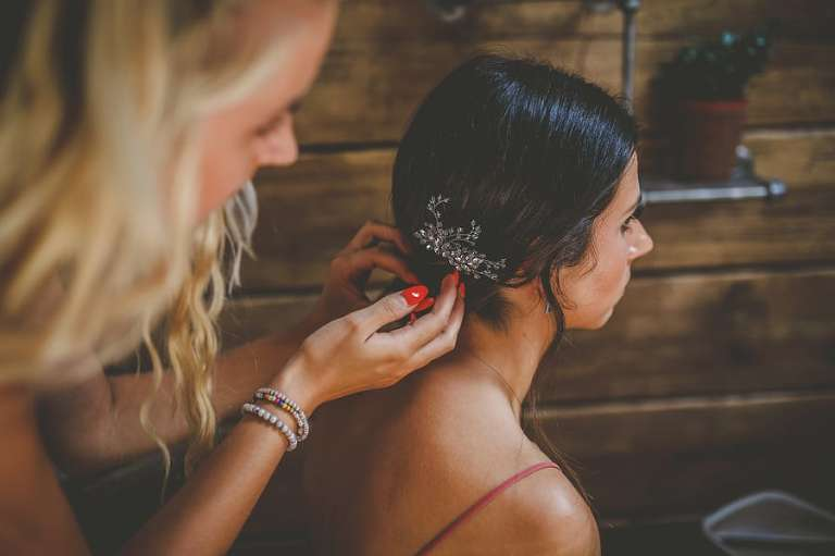 The hairdresser places a clip on the back of the brides hair as she sits down in the cottage