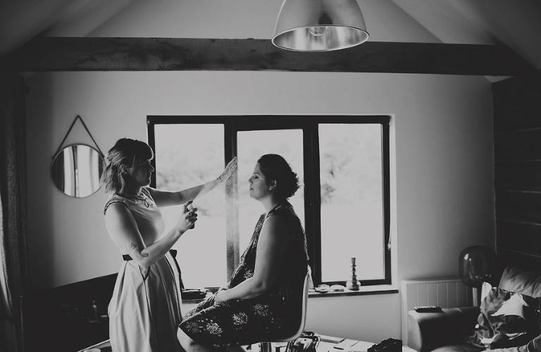 The makeup artist sprays a bridesmaid face as she sits down in the cottage