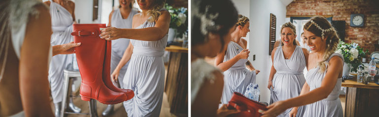 Bridesmaids give the bride a new set of red wellington boots in the kitchen of the cottage