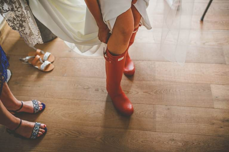 The bride puts on her new red wellington boots in the kitchen of the cottage