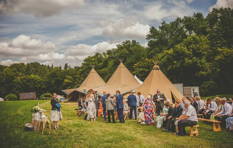 Wedding guests gather in the field next to the large tipi for the outdoor wedding ceremony at Yurt retreat in Crewkerne