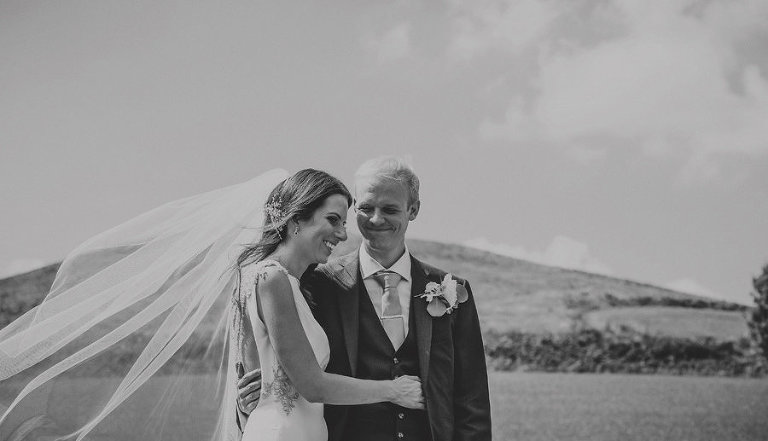 The groom smiles at the bride and puts his arm around her during the wedding ceremony