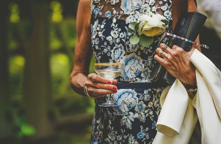 The grooms mother holds a glass of champagne in her right hand
