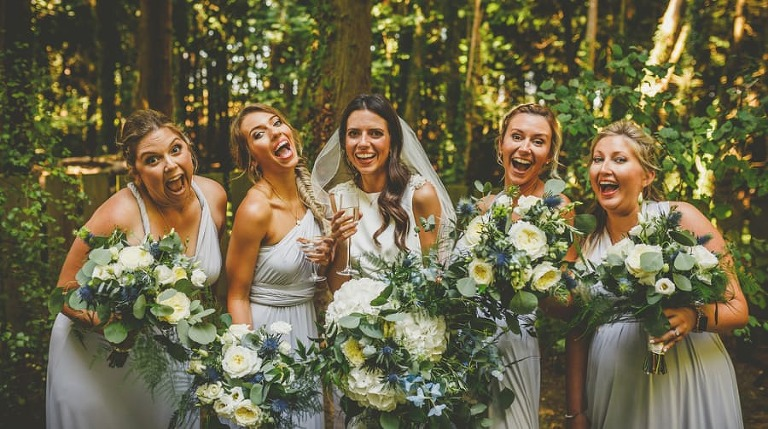 The bride and bridesmaids pose for a photograph with their bouquets