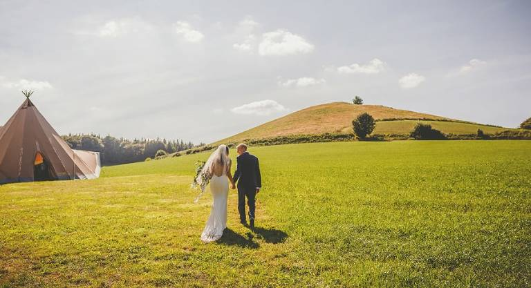 The bride and groom hold hands and walk towards the large tipi in the field at yurt retreat