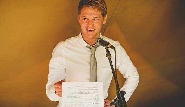 The best man holds a piece of paper in his hand and delivers his speech to the wedding guests in the tipi