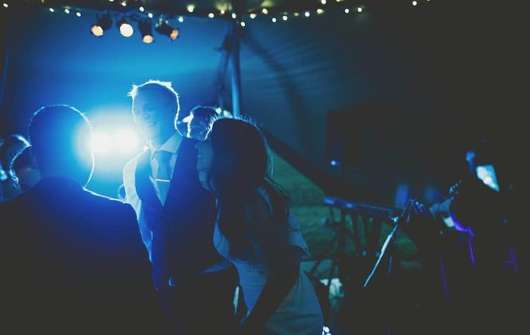 The bride dances with the groom on the dancefloor
