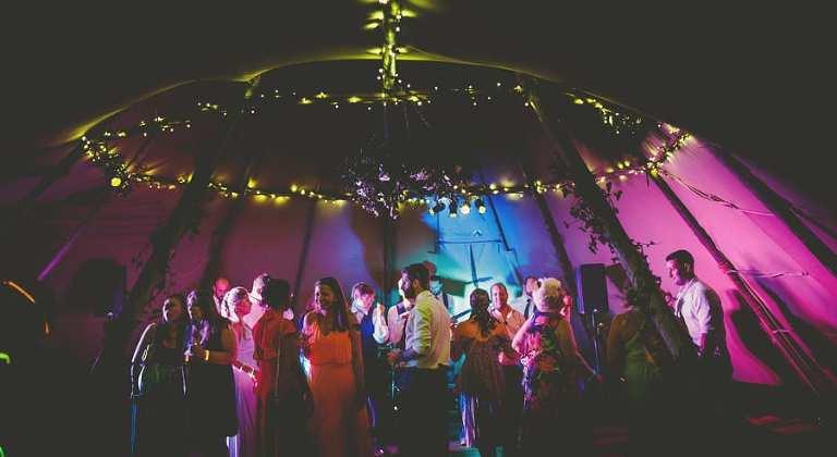 Wedding guests on the dancefloor in the tipi at yurt retreat