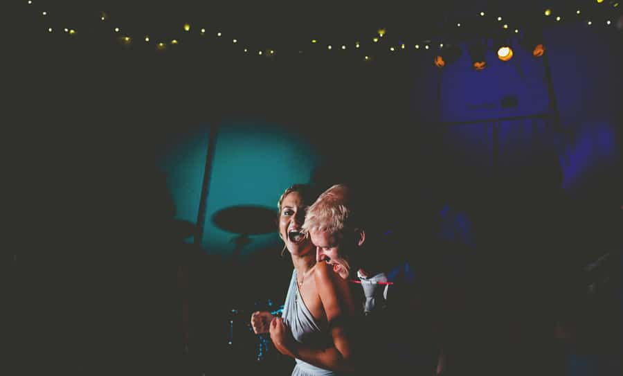 The groom puts his arms around a bridesmaid on the dancefloor in the tipi at yurt retreat