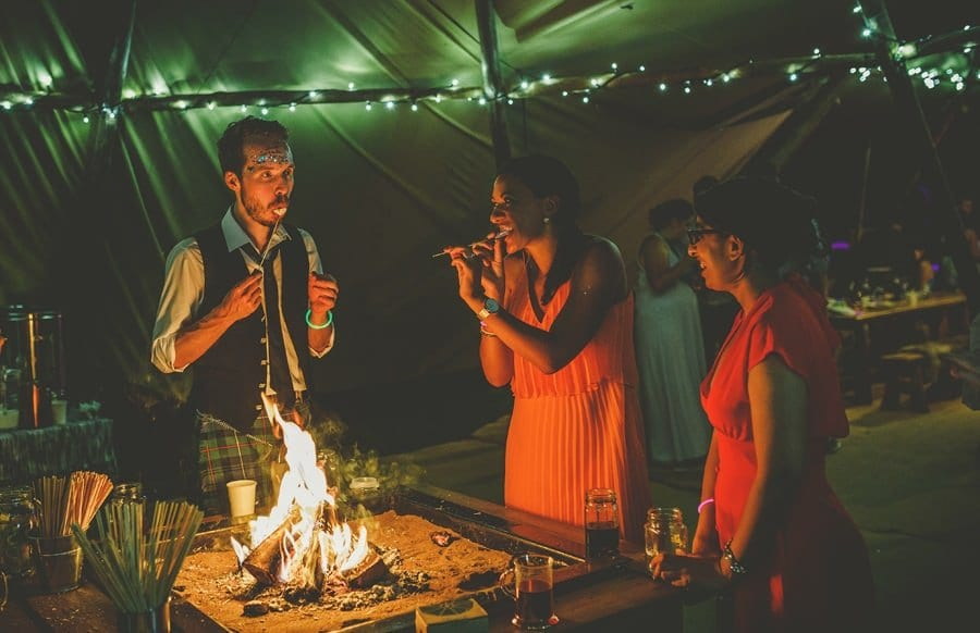 Wedding guests toast marshmellows over an open lit fire in the tipi