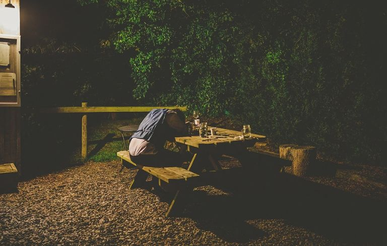 A man lies asleep on a wooden bench outside the tipi at yurt retreat in Crewkerne
