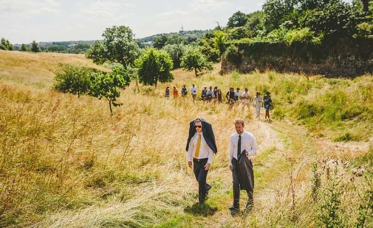 Wedding guests walking through a field towards the wedding venue