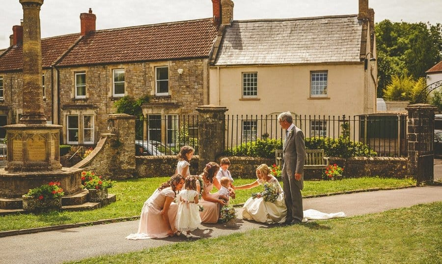 The bride and her father are greeted in the gardens of the Church by the flowergirls and bridesmaids