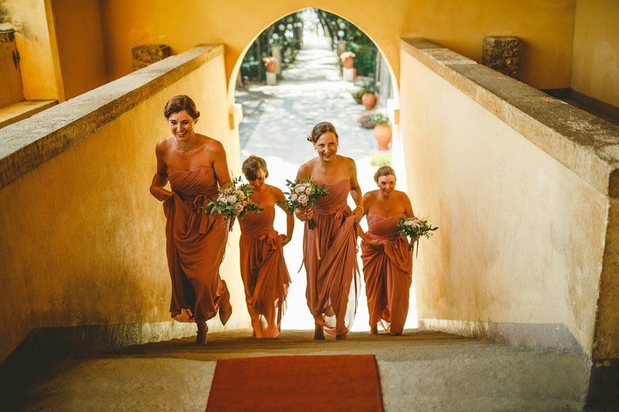 Bridesmaids walking up stone steps towards the wedding ceremony holding their bouquets