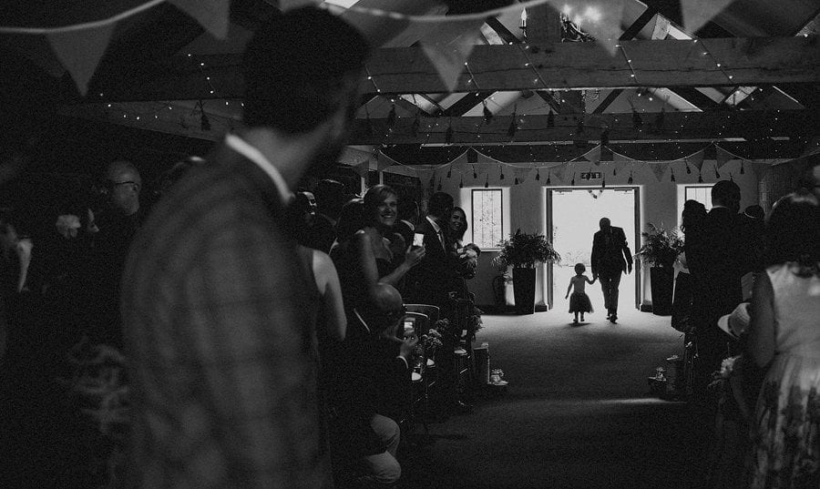 A flower girl walks towards the groom holding her grandfathers hand