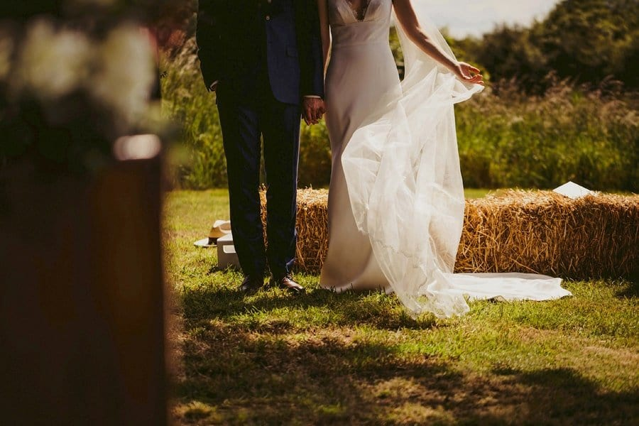 The bride moves her veil to one side as she stands next to the groom during the outdoor ceremony in a field