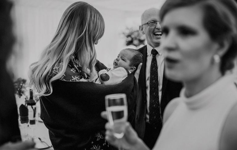 A lady holds her baby boy in her arms next to wedding guests in a marquee