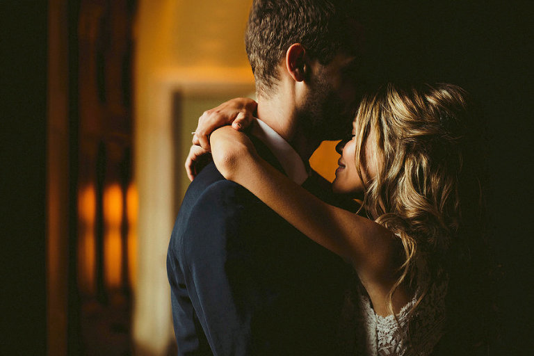 The groom kisses the bride on the forehead as she wraps her arms around his shoulders