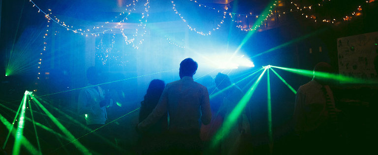 The bride and groom stand next to each other on the dancefloor of the marquee and watch people dancing