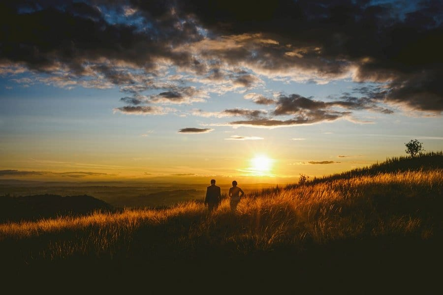 A bride and groom walk through grass next to each other on a hill as the sun goes down in the distance