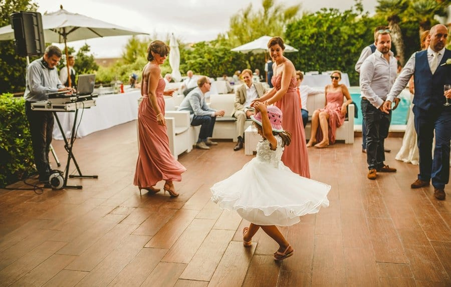 A flower girl dances with bridesmaids