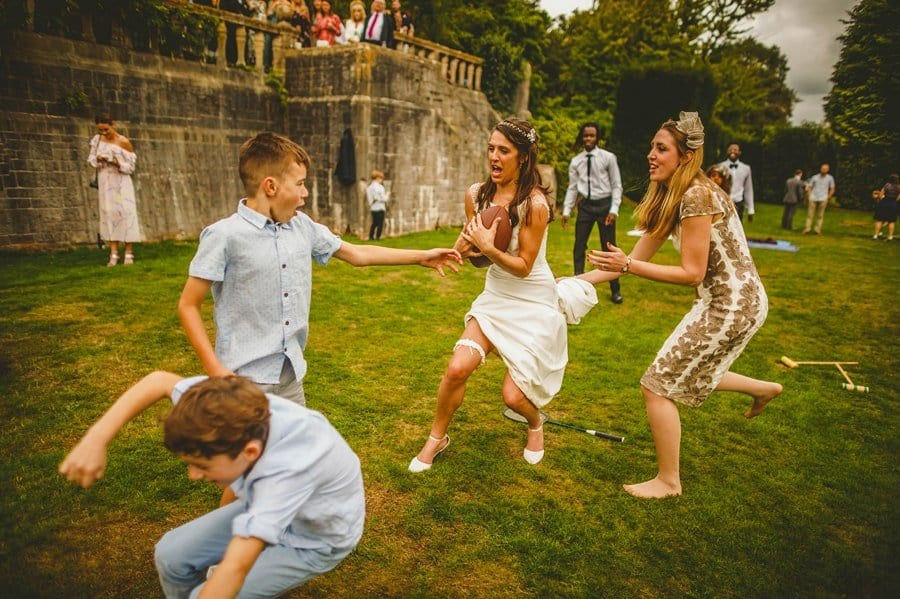 A bride runs across a lawn with wedding guests holding an American football
