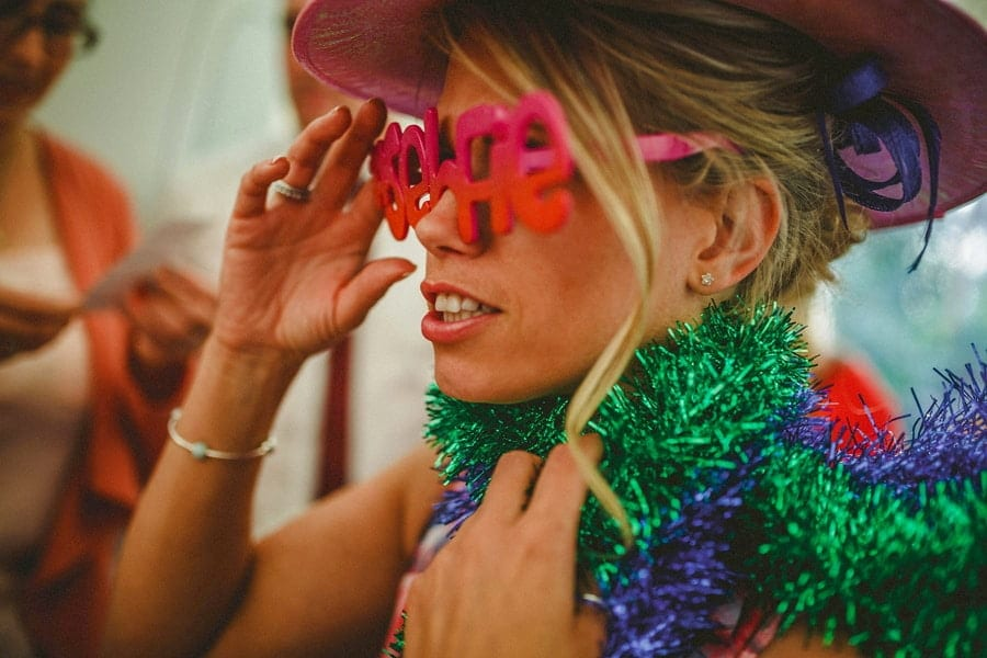 A lady wears a pink hat and holds her sunglasses in her right hand and wraps tinsel around her neck