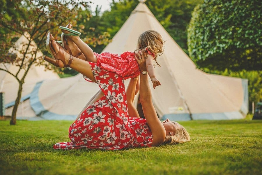 A lady lies on the grass in front of a tipi and lifts a little girl up in the air