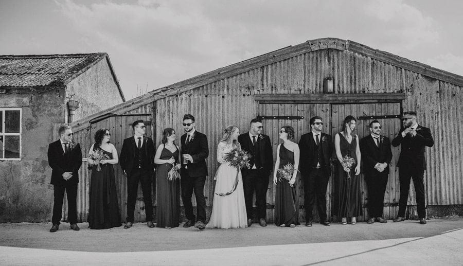 The bride and groom stand in front of large shed and talk with the wedding party