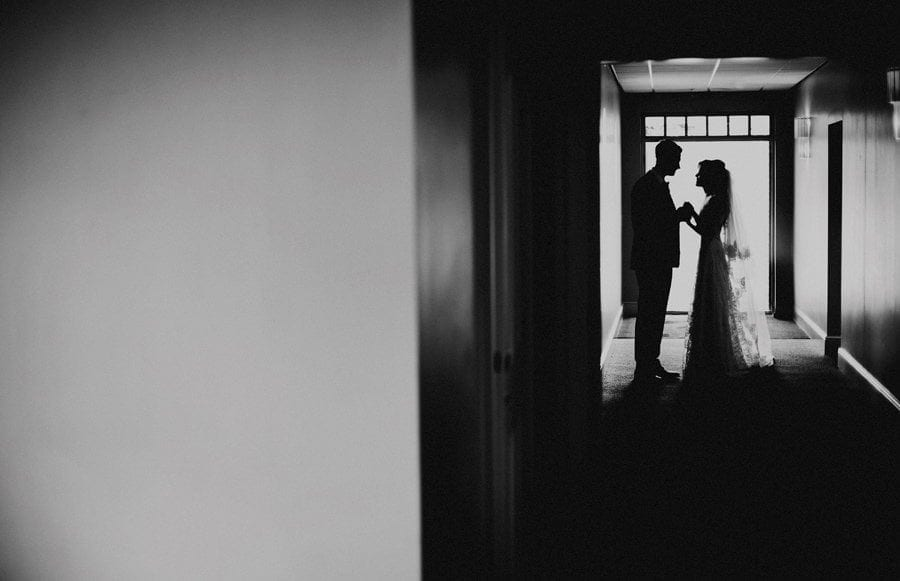 The bride and groom stand in a corridor and hold hands as they look each other
